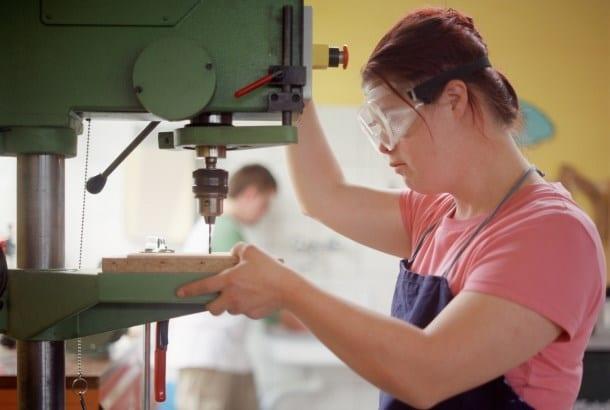jonge vrouw met downsyndroom met beschermbril bedient een grote boormachine