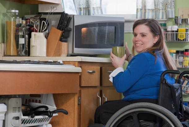 Vrouw in rolstoel in keuken