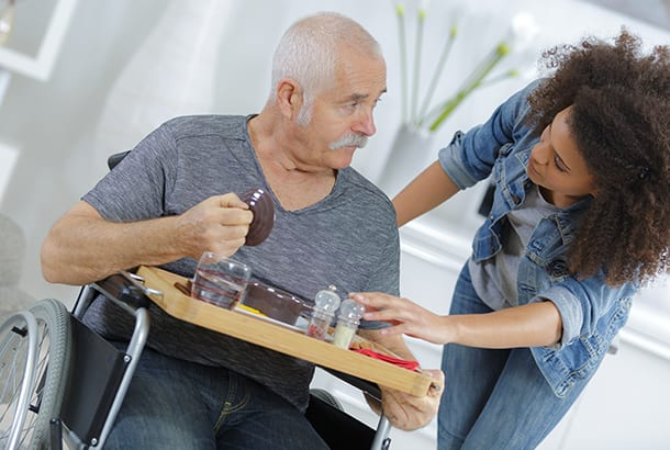man in rolstoel met eten op dienblad geadviseerd door vrouw