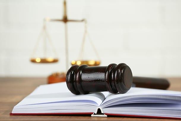 Voorzittershamer op een boek_met juryevenwicht op achtergrond
