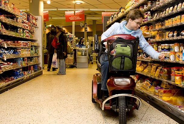 Vrouw in scootmobiel doet boodschappen in supermarkt
