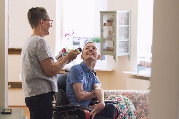 Jongen thuis in rolstoel met hulp