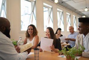 Bijeenkomst waarbij verschillende mensen aan tafel zitten, waaronder een vrouw met het syndroom van down