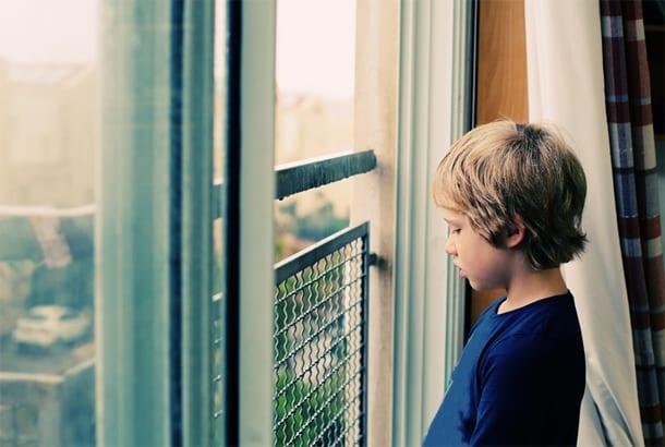 Jongetje kijkt mistroostig vanachter het raam naar buiten