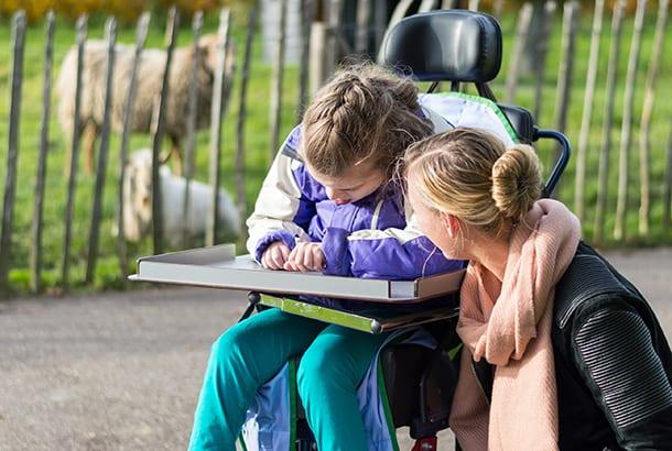hulpverleenster met meisje met ernstig meervoudige beperking in rolstoel buiten bij de dierenweide