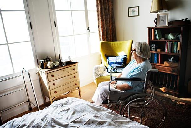 vrouw in rolstoel in kamer zorginstelling