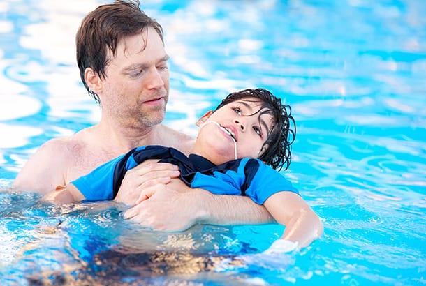 Gehandicapt kind met vader in zwembad