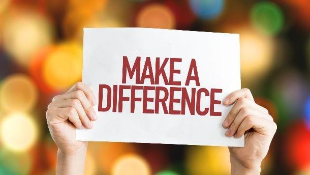 Twee handen houden bord omhoog met tekst Make a difference