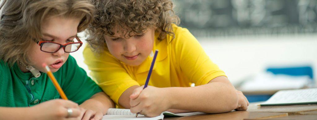 Twee kinderen aan tafeltje met potlood in de hand gebogen over een schriftje