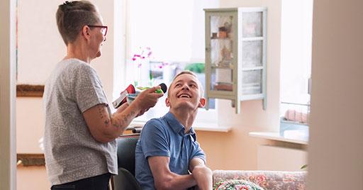 vrouw verzorgt jongen in rolstoel