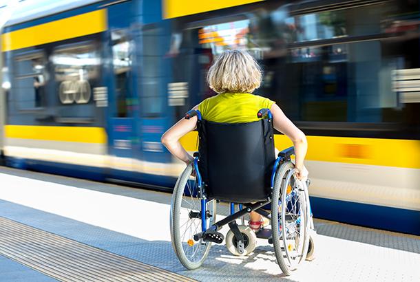 Vrouw in rolstoel staat bij trein
