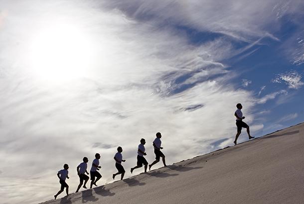 Groep mensen loopt een berg op, een sporter is een koploper