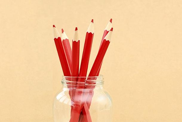 Illustratief: rode stempotloden in een potje