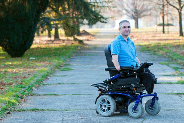 Man in elektrische rolstoel in het park