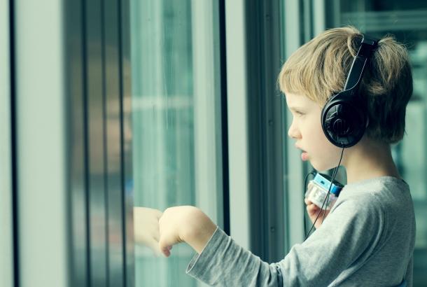 Illustratief: jongen met koptelefoon kijkt naar buiten terwijl hij de ruit aanraakt.