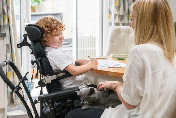 moeder met zoontje in rolstoel aan tafel thuis