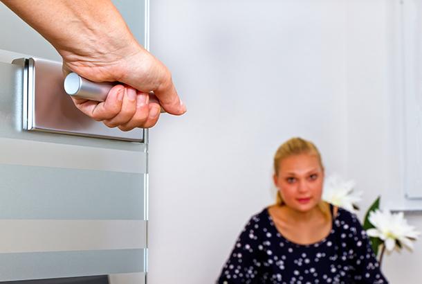 hand zorgvverlener opent deur, vrouw zit daarachter