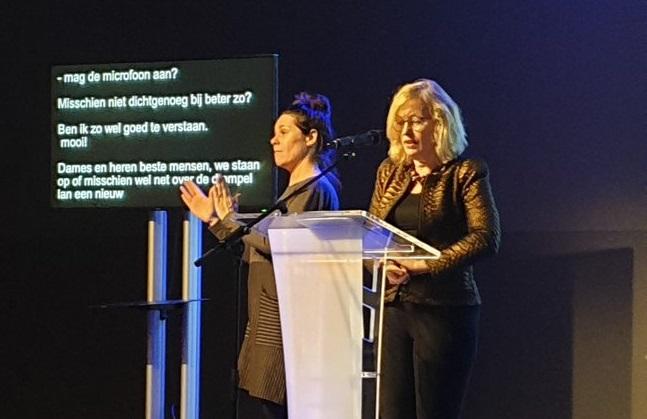 Jet Bussemaker begint haar speech, rechts van haar de gebarentolk