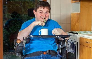 Man met celebrale parese in rolstoel drinkt met rietje uit een mok