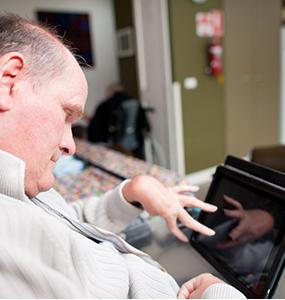 Man met beperking werkt op de i-pad