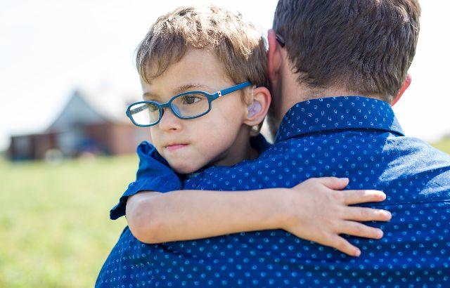 jongetje met gehoorapparaat en bril samen met zijn vader