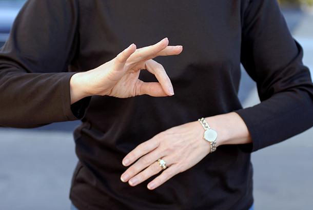 Illustratief beeld. Het gebaar voor ' ok' wordt door vrouw in zwart shirt gemaakt.