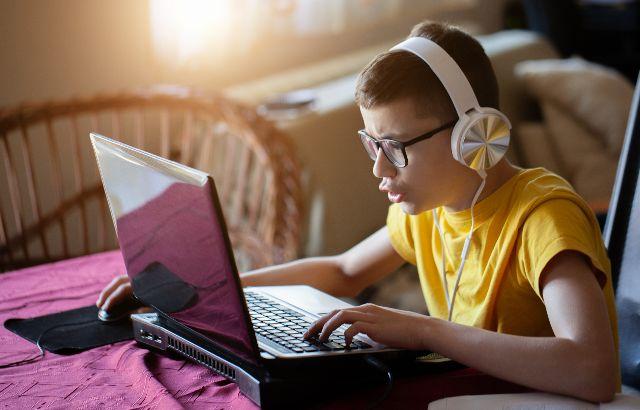 jongen achter laptop met koptelefoon op