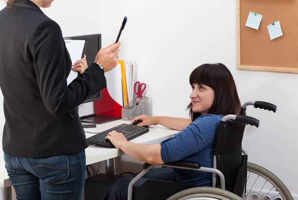 ongevrouw in rolstoel_achteJonge vrouw in gesprek met leidinggevende