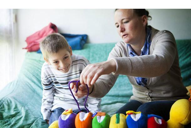 Kind met moeder spelend op de bank
