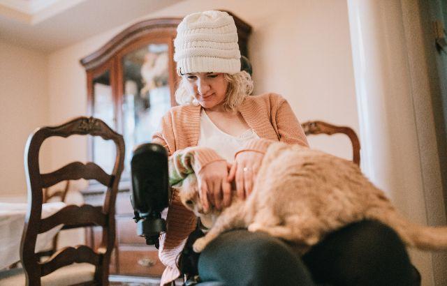 jonge vrouw in rolstoel thuis met poes op schoot
