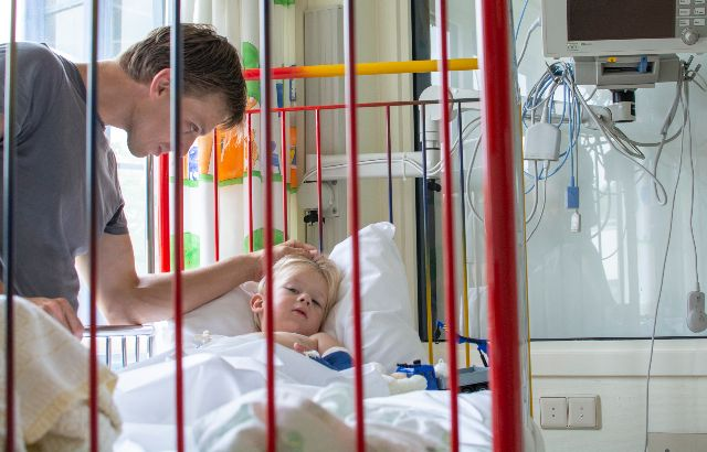 kind in ziekenhuisbed met vader
