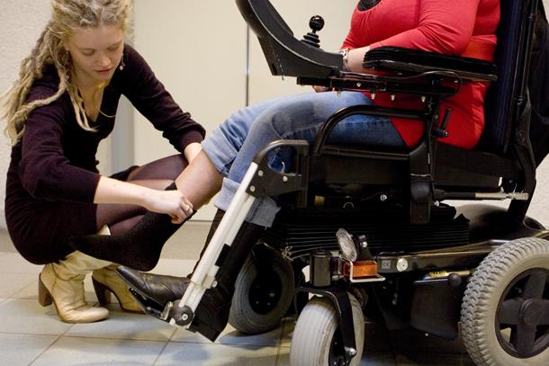 hulpverleenster helpt iemand in rolstoel met aankleden