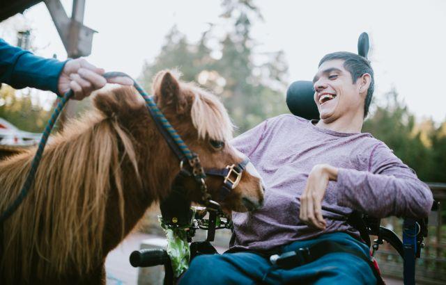 man met spasme in rolstoel bij klein paard