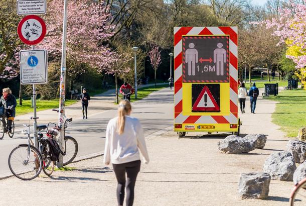 Houd afstand van 1.5 meter, lopend en fietsend in openbaar park Amsterdam