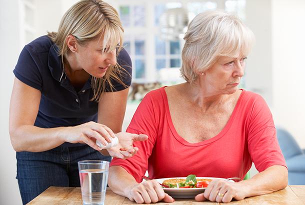 VVrouw met bord met eten voor zich wordt medicijnen aangeboden, waar zij zich van afkeert