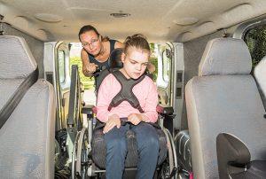 Vrouw zet meisje in rolstoelbusje
