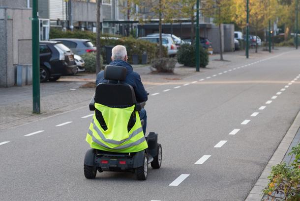 Iemand die een scootmobiel berijdt gezien van achterkant