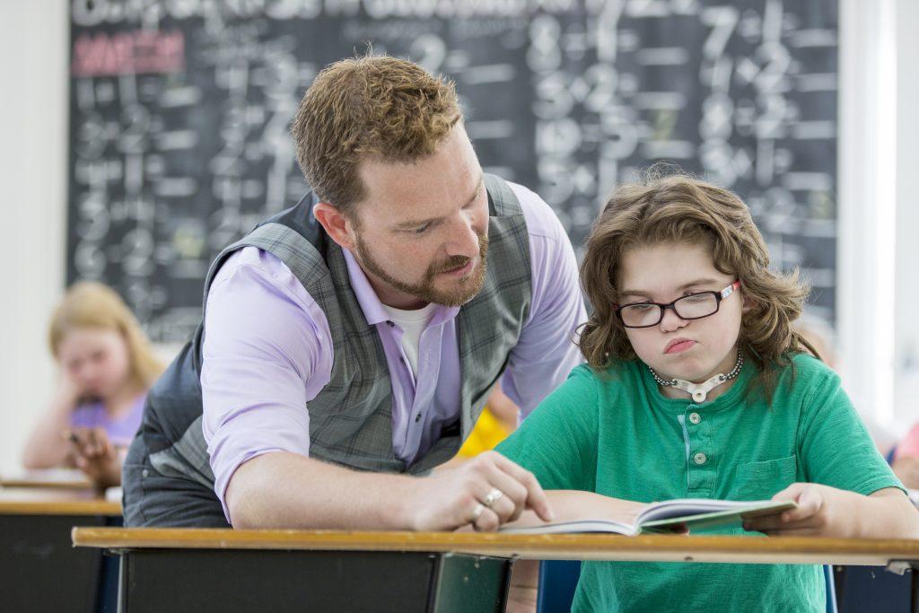 Leraar helpt iemand met beperking in de klas
