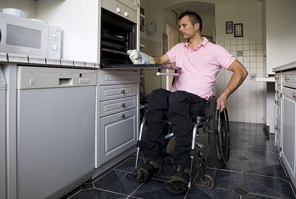 illustratief beeld: man in rolstoel in keuken gebruikt oven
