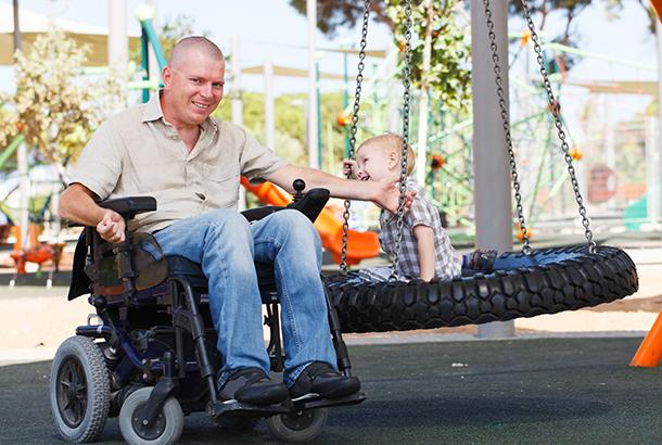 Man in rolstoel met zijn kind in een speeltoestel