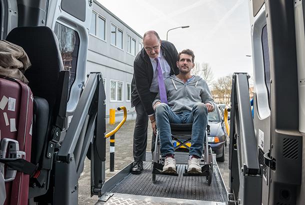 jongeman in rolstoel wordt in busje geholpen door de chauffeur