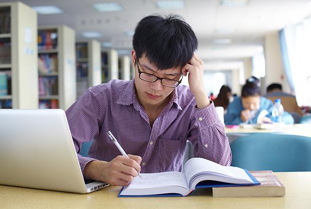 student achter laptop die notities maakt