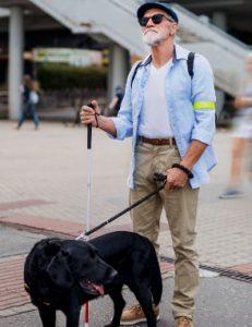 Blindeman met geleidehond staande buiten in de stad
