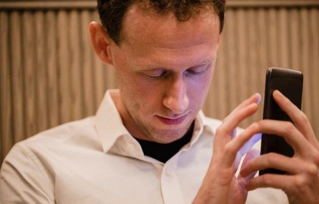 Man met mobiele telefoon in hand