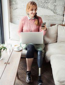 Vrouw met prothesebeen zittend op de bank, werkend achter een laptop_lokaal aan de slag