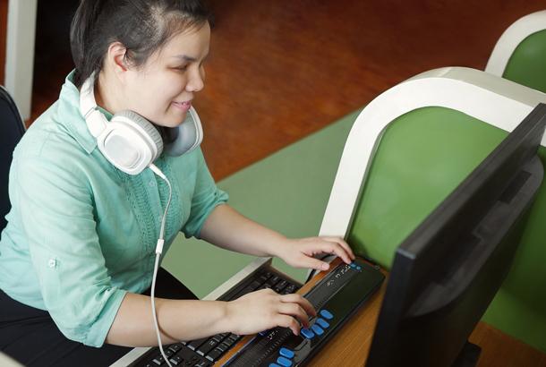 Jonge blinde vrouw met hoofdtelefoon die met behulp van computer met vernieuwbare brailleleesregel