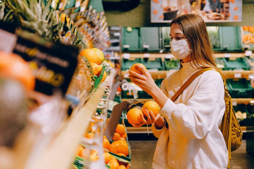 Jonge dame bij de groenteafdeling in de supermarkt. Ze draagt een mondkapje