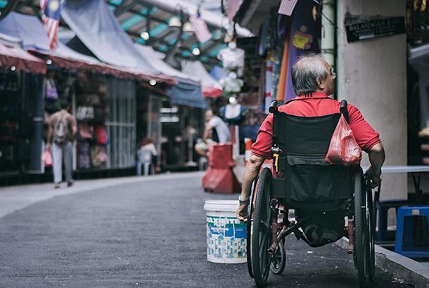 man in rolstoel in winkelstraat