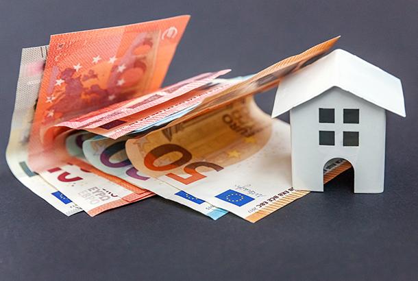 Illustratief: huisje met papiergeld er om heen