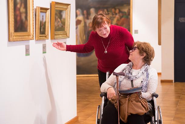 Vouw in rolstoel die een museum bezoekt (met begeleiding)